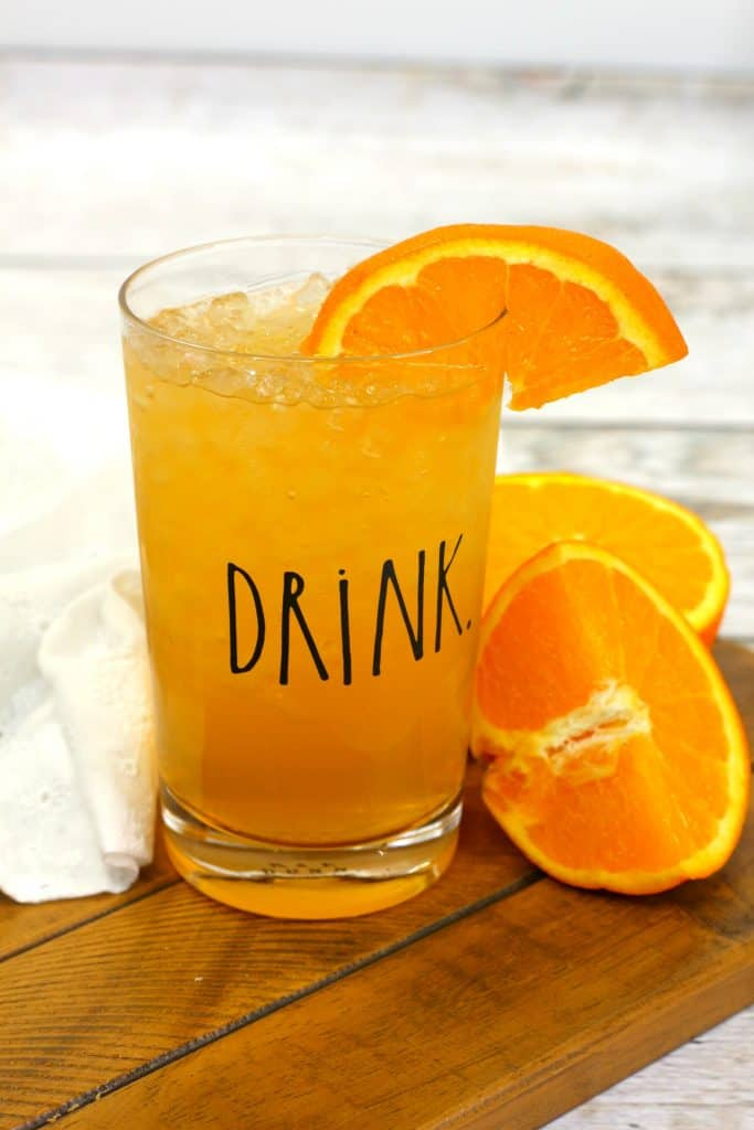 energy drink in a clear glass with a drink label on it, with a slice of orange in the drink and oranges next to it.