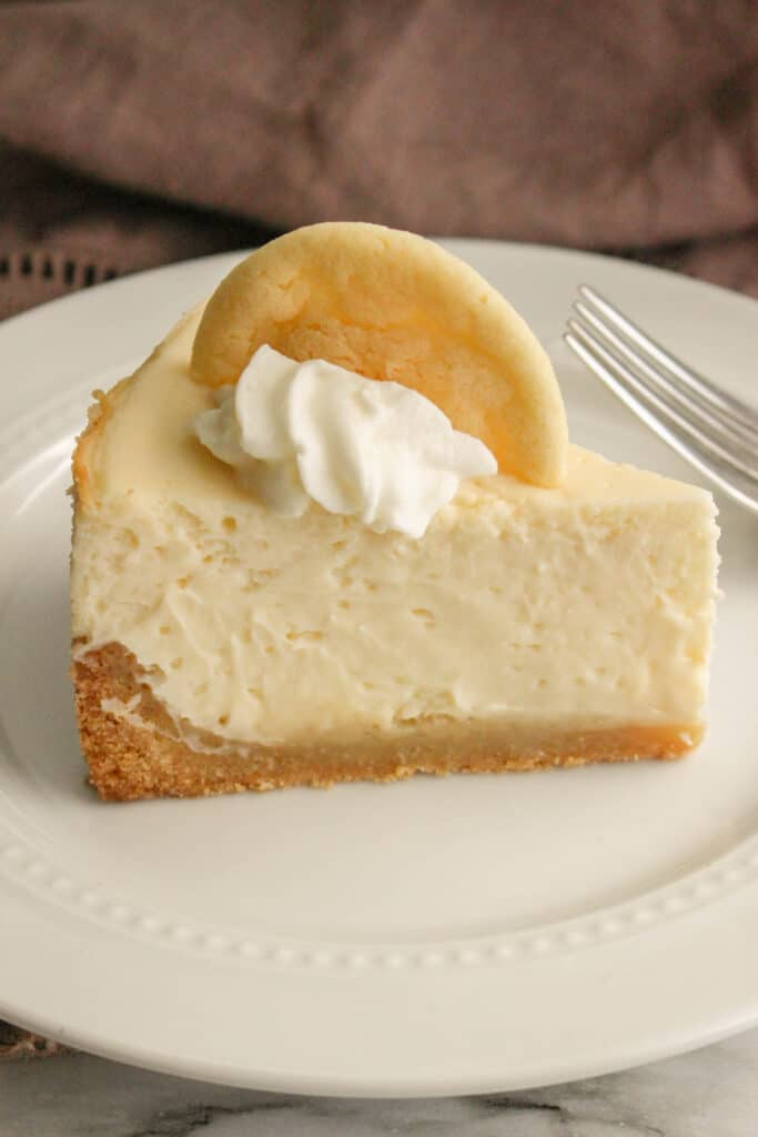 Instant Pot Sugar Cookie Cheesecake on a white plate with a brown towel in the background.