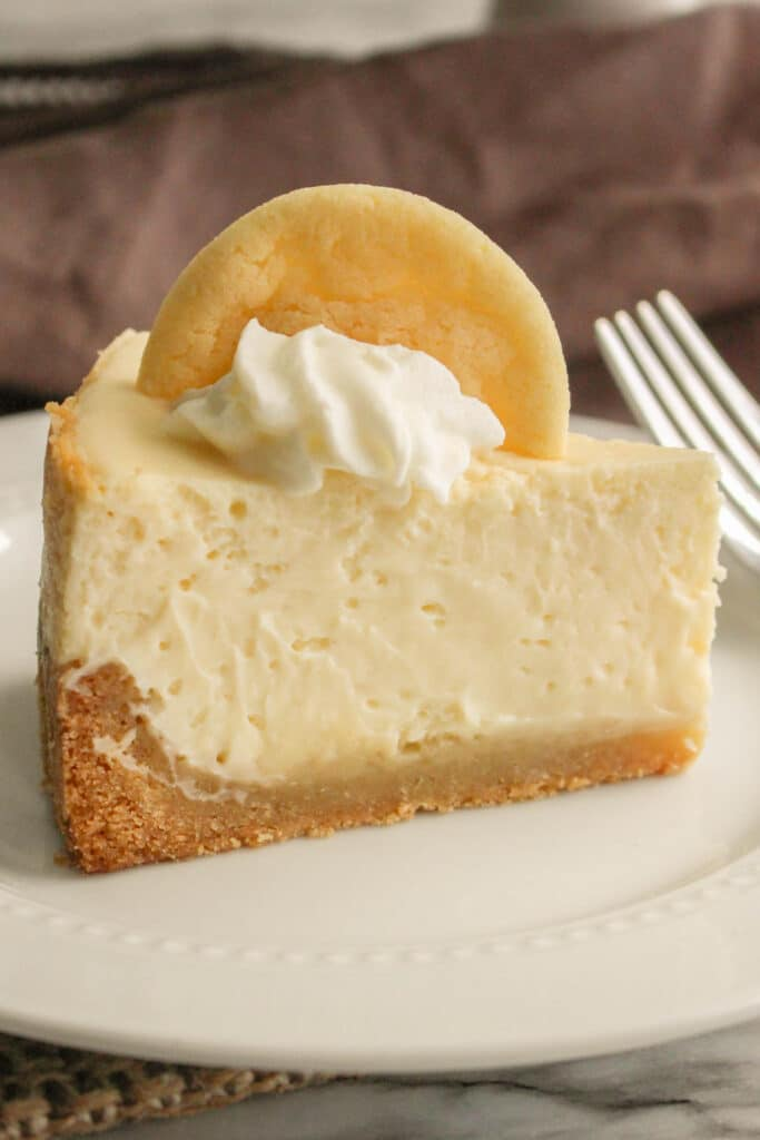 Close up eye level image of a slice of cheesecake on a white plate with a sliver fork.