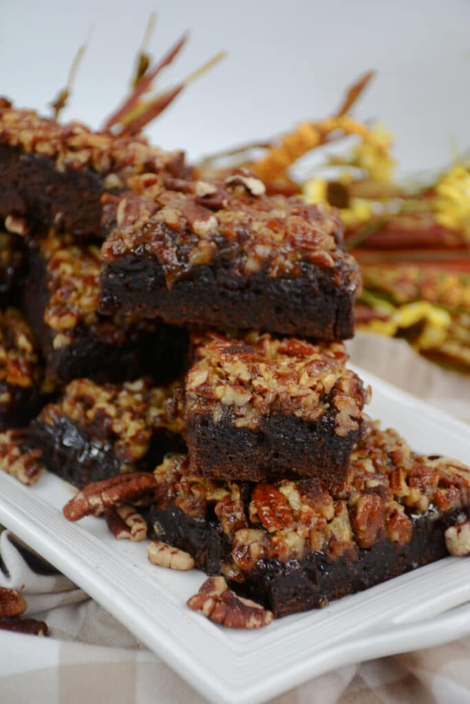 vertical image of pecan pie brownies stacked on a rectangle shaped white platter