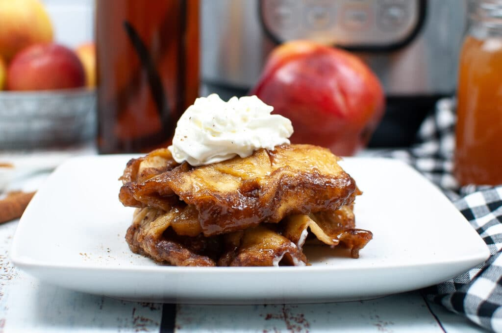 Horizontal Image of apple dumplings with an apple in the background and instant pot.