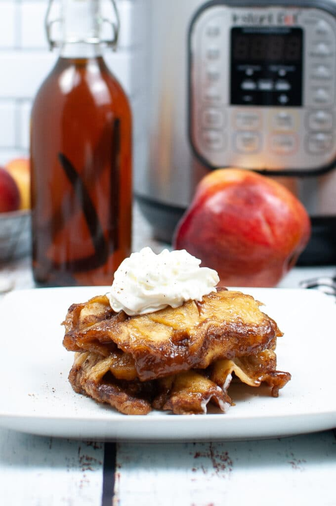 Vertical Image of Instant Pot Apple Dumplings with apple and jar of vanilla extract in background